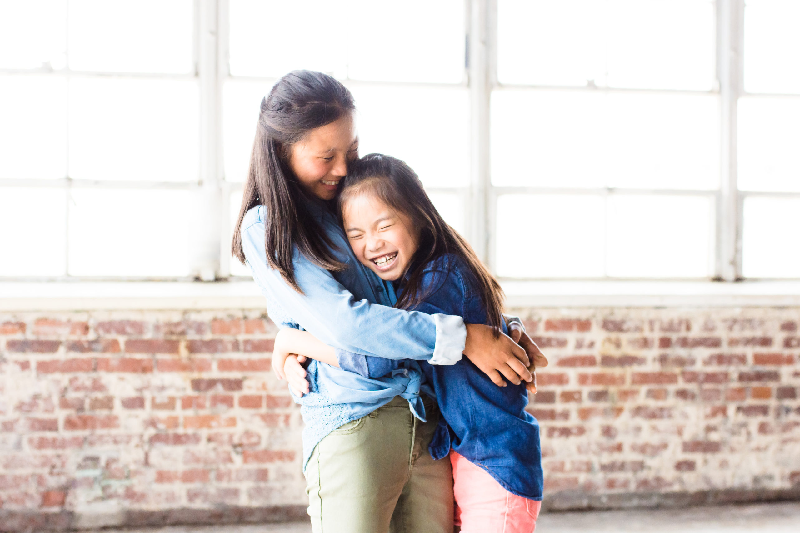 Two young girls hugging and laughing