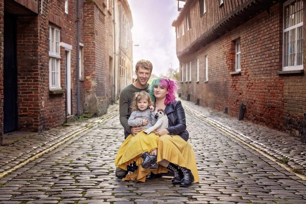 Brett and Kacie Malloch pose with their young daughter for a family photo in an alley